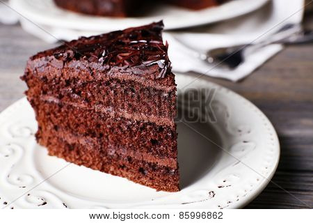 Delicious chocolate cake in white plate on wooden table background, closeup