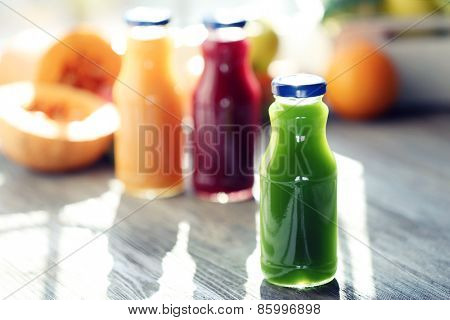 Bottles of juice with fruits and vegetables  on windowsill close up