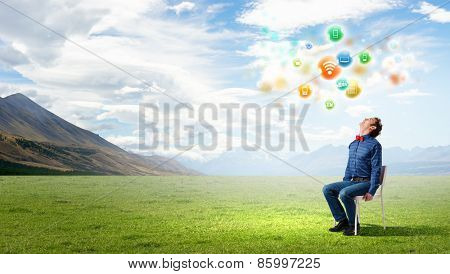 Young funny guy sitting in chair and looking upwards