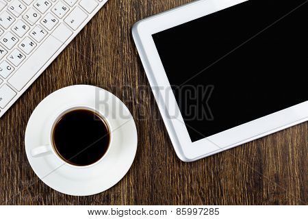 Tablet pc cup of coffee and keyboard on table