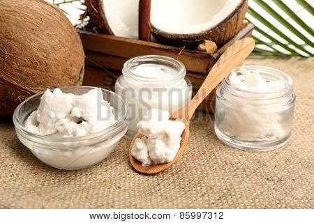 Coconut with jars of coconut oil and  cosmetic cream on sackcloth background