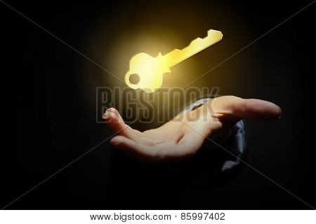 Close up of human hand holding golden key