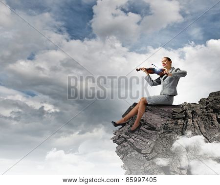 Young businesswoman sitting on rock and playing violin