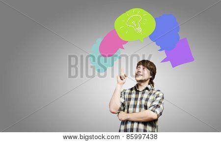 Young thoughtful man and colorful speech bubbles above