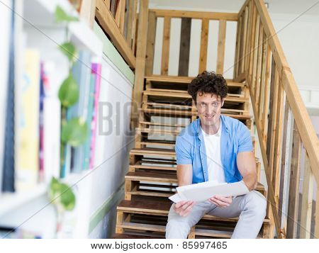Man sitting with papers on the stairs