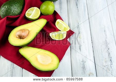 Avocado with limes on napkin on wooden background