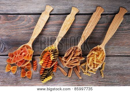 Different types of pasta in spoons on wooden background
