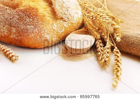 Fresh bread with wheat and wooden spoon of flour isolated on white