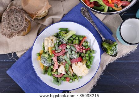 Frozen vegetables on plate on napkin, on wooden table background
