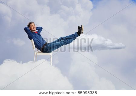 Young man sitting in chair with legs up and relaxing