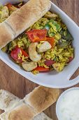 pic of curry chicken  - Bowl with curry flavored rice chicken and vegetables on rustic wooden table