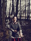 image of archer  - Medieval archer woman she wearing a chainmail and use a bow and arrow gloomy forest cross - JPG