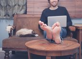 pic of working animal  - A happy barefoot man is resting his feet on a coffee table at home while working on his laptop there is a cat sleeping next to him - JPG