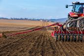 stock photo of plowing  - Sowing and plowing action in the spring season - JPG