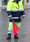 image of policeman  - policeman in uniform with the red flag to signal the roadblock - JPG