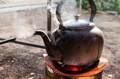 stock photo of boiling water  - old kettle for boiling water on charcoal stove - JPG