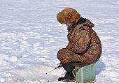 stock photo of siberia  - Fisherman on ice fishing on the reservoir in eastern Siberia - JPG