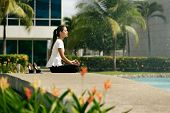 foto of hispanic  - Young stressed hispanic business woman doing yoga outside office building sitting in lotus position with hands on knees in the street - JPG