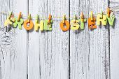 image of clotheslines  - German text Happy Easter hanging on clothesline over white wooden board - JPG