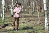 picture of early-man  - young man walks in the early spring in a lush park  - JPG