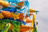 stock photo of pinata  - Pinatas stacked for sale in the sunlight - JPG