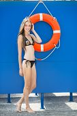 picture of lifeguard  - Woman on the beach near lifeguard tower and lifebuoy - JPG