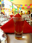 stock photo of mezcal  - A shot of mezcal served in a traditional mexican party. ** Note: Shallow depth of field - JPG