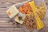 picture of sackcloth  - Different types of pasta on sackcloth on wooden background - JPG