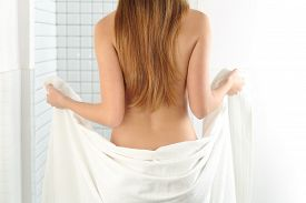picture of douching  - Back view of a woman body entering in the shower with a white towel - JPG