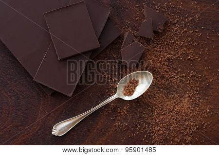 Close Up Of  A Silver Spoon, Cocoa Powder And Chocolate From Above - Studio Shot
