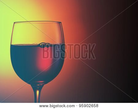 glass of red wine on dark red background.Filtered image: cool cross processed vintage effect.
