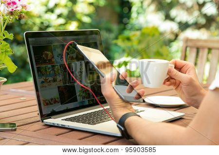 young man working from garden wooden table using notebook computer
