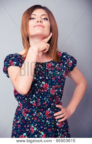Young woman showing threatening gesture over gray background