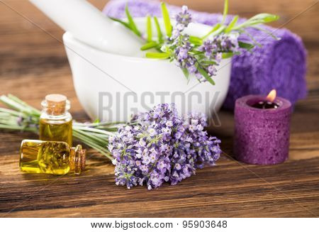 Lavender oil, herbal towel and fresh lavender flowers on wooden background. Wellness still-life.