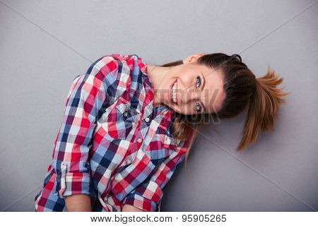 Funny cute woman with ponytail looking at camera over gray background