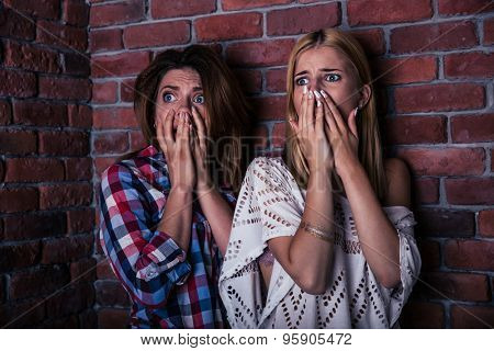Two scared woman standing with brick wall on background