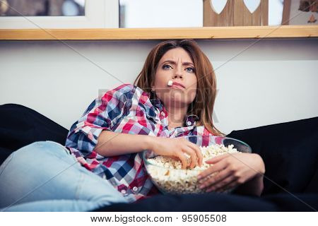 Young woman lying on the sofa and eating popcorn at home
