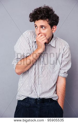 Scared young man covering his mouth over gray background