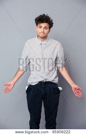 Handsome man shrugging and showing his empty pocket over gray background. Looking at camera