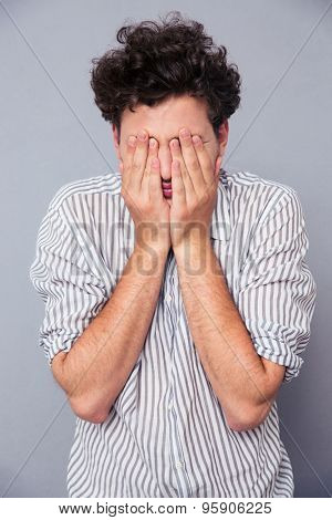 Young man covering his face with palms over gray background