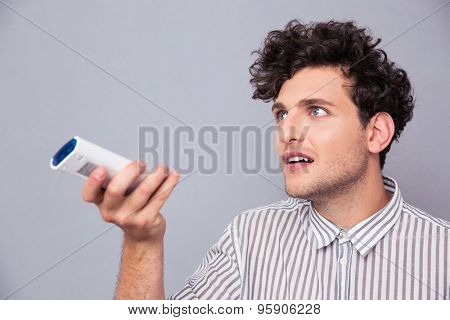 Man holding TV remote over gray background