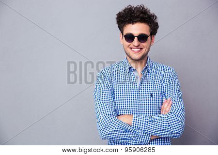 Happy fashion man wearing in sunglasses standing with arms folded over gray background