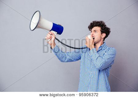 Young casual man shouting on megaphone over gray background