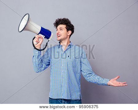 Young casual man screaming on megaphone over gray background