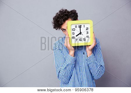 Man covering his face with big clock and looking at camera over gray background