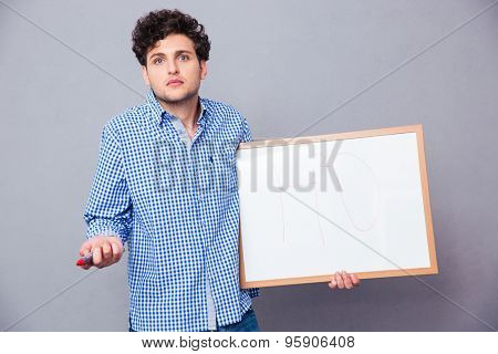 Young male student holding text board with marker and shrugging