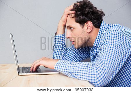 Side view portrait of a serious man sitting at the table and using laptop