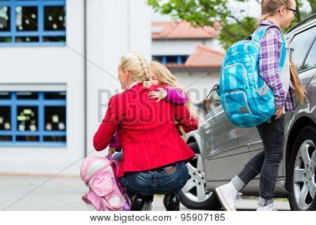 Mother hugging child after bringing her to school