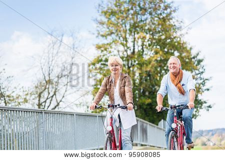 Senior couple, married woman and man, riding their bicycles over a bridge enjoying some leisure time