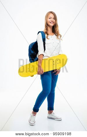 Full length portrait of a happy female student holding skateboard isolated on a white background